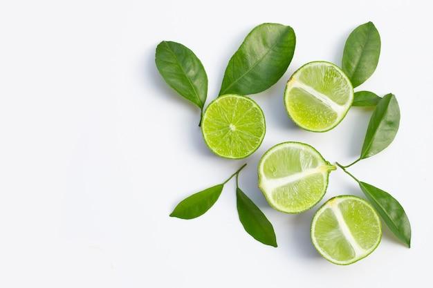 Свежие лаймы с зелеными листьями на белой поверхности. вид сверху