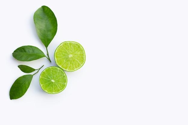 Свежие лаймы с зелеными листьями. вид сверху