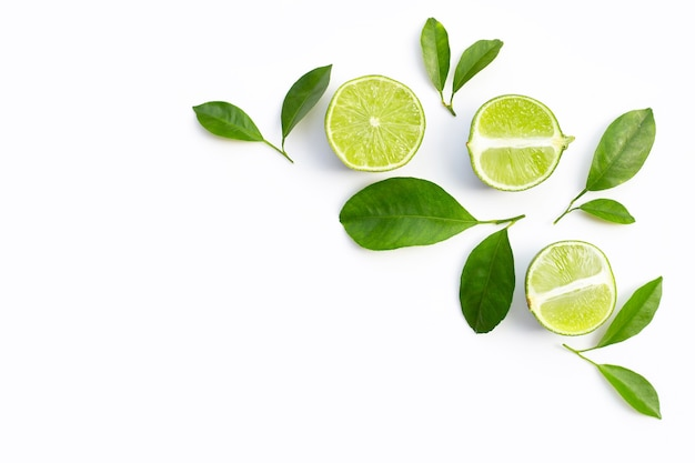Fresh limes with green leaves on white background. top view