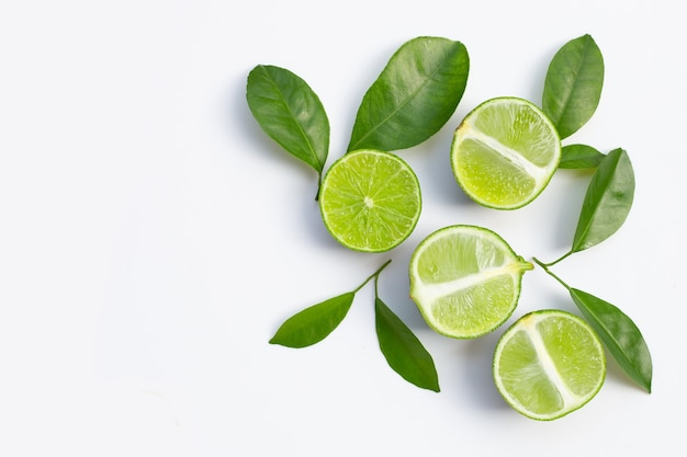 Fresh limes with green leaves on white surface. top view