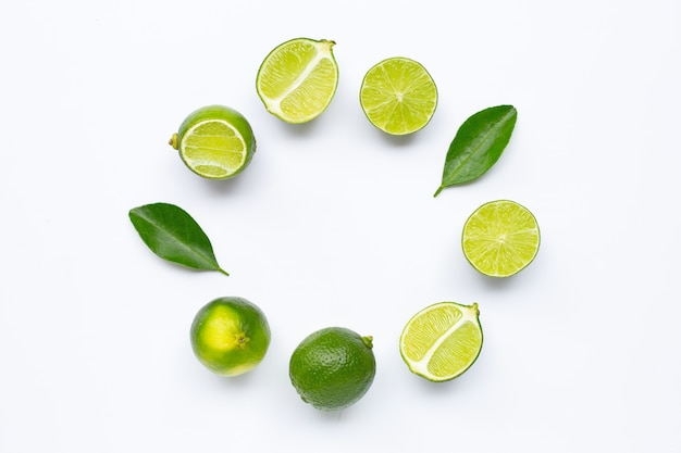 Fresh limes with leaves, rounded frame composition for background