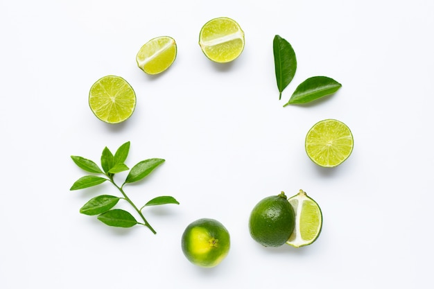 Fresh limes with leaves, rounded frame composition on white background