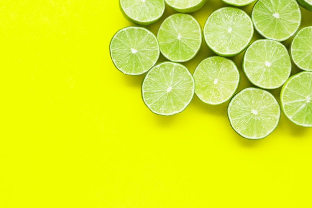Fresh limes with on yellow background.