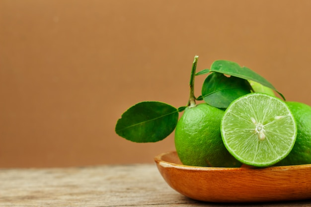 Fresh limes in wooden bowl on wooden background