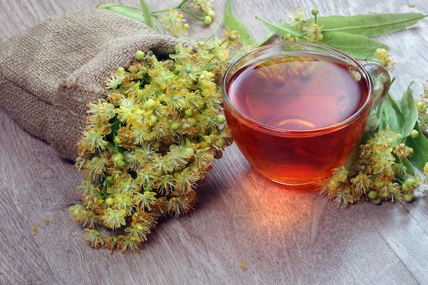 Свежие цветы липы в сумке и чашка чая липы на деревянном столе.