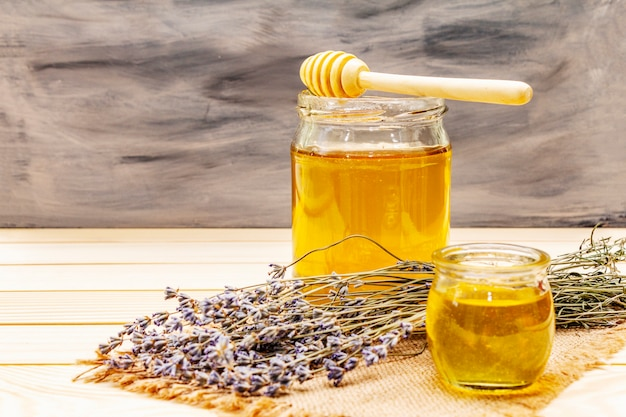 Fresh liquid honey in glass jars with a wooden honey dipper