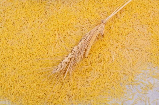 Piccoli vermicelli freschi con grano su uno spazio bianco.