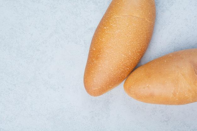 Свежий хлеб буханки на синем фоне. фото высокого качества