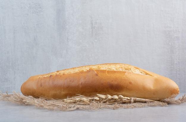 Свежий хлеб буханки на мешковине с пшеницей. фото высокого качества