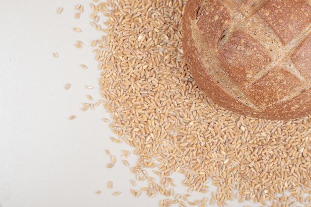 Свежая буханка хлеба с овсяными зернами на белой поверхности