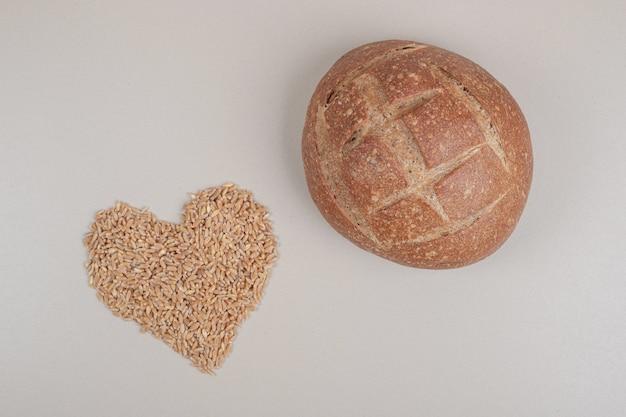 흰색 표면에 귀리 곡물과 빵의 신선한 덩어리