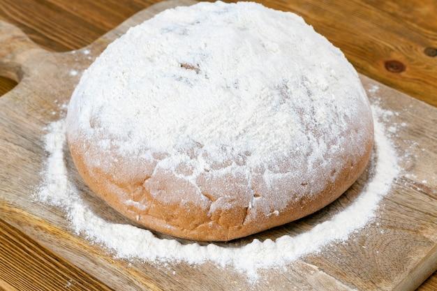 양질의 흰 밀가루를 뿌린 신선한 호밀 빵