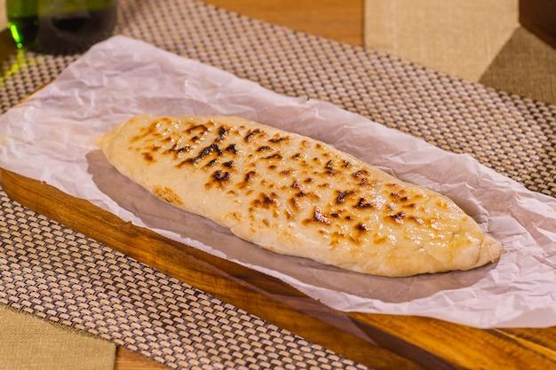 有機包装の木製テーブルの上の新鮮なロビアーニとハチャプリ。伝統的なグルジアのペストリーと料理。