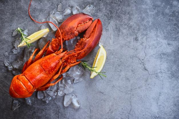Свежая еда омаров на черном фоне - ужин из красного омара морепродукты со специями из трав лимонный розмарин подается стол и лед в ресторане для гурманов здоровая вареная омаров приготовленные