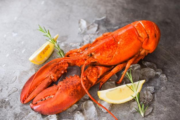 ブラックプレートの背景に新鮮なロブスターフード/ハーブロブスターレモンローズマリーと赤いロブスターディナーシーフードテーブルで提供し、レストランでアイスグルメ食品ヘルシーゆでロブスターを調理