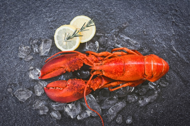 黒い皿に新鮮なロブスター料理。赤いロブスターディナーシーフードハーブスパイスレモンローズマリーレストランでテーブルと氷を提供グルメ料理健康的なゆでロブスター調理
