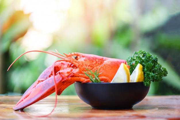 ボウルと自然の新鮮なロブスター料理。赤いロブスターディナーシーフードハーブスパイスレモンローズマリーテーブルとレストランでグルメ料理ヘルシーなゆでロブスター調理