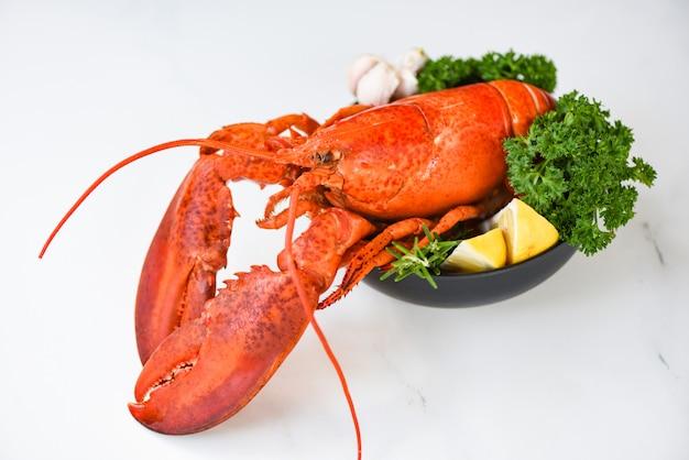 ボウルと白いテーブルの背景-ハーブスパイスレモンローズマリーと赤いロブスターディナーシーフードの新鮮なロブスター料理とレストランでグルメ料理ヘルシーゆでロブスターを調理