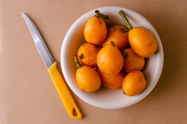 Fresh loquats on white plate and knife on beige