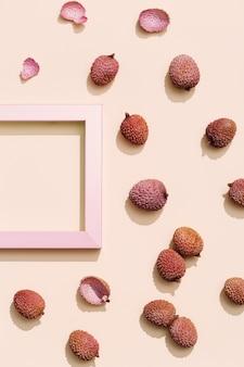 パステルベージュの背景に新鮮なライチの果実。最小限の果物と夏のコンセプト。