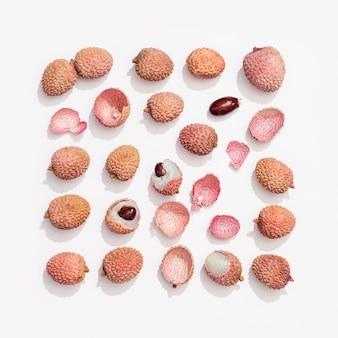 白い背景の上の新鮮なライチの果実。長方形に刻まれたフードパターン。上から見る