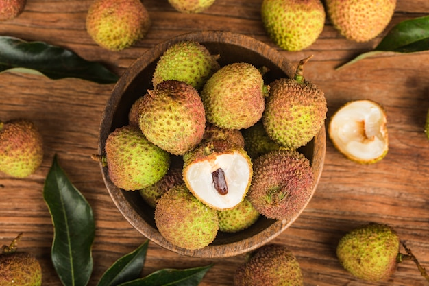 Fresh lychees on a wooden board background