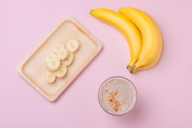 분홍색 배경에 유리에 신선한 바나나 스무디