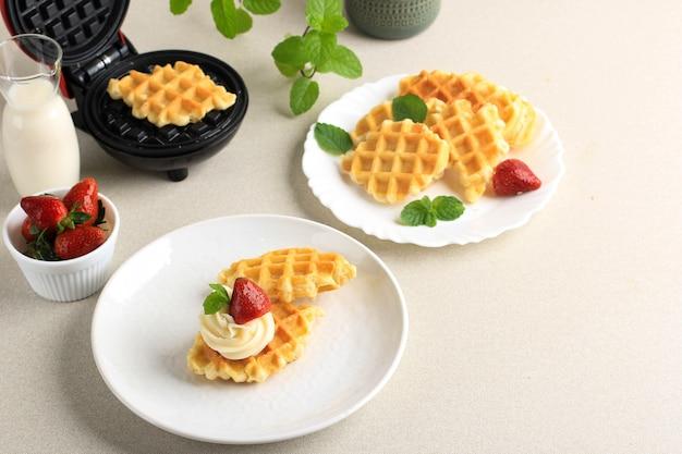 生クリームとイチゴの作りたてのおいしい自家製クロワッサンワッフル。上に。白いプレートで提供され、テキスト用のコピースペースできれいな背景