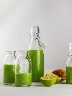 Fresh made healthy green smoothie served in bottles on white background.