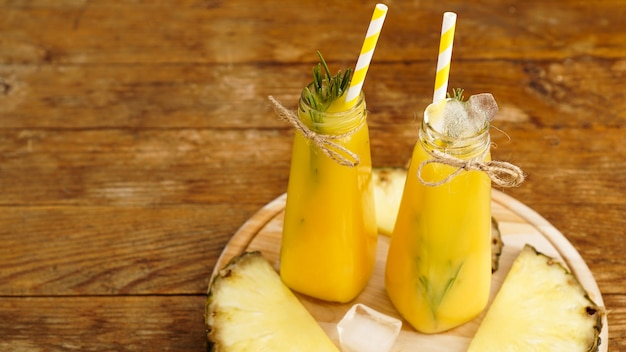 Fresh made pineapple juice with ice in a small glass bottle
