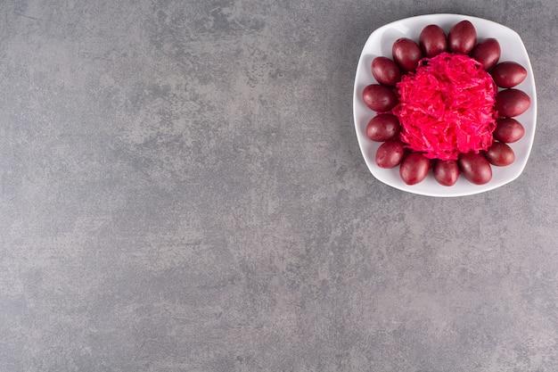붉은 양배추 샐러드의 신선한 부분을 돌 테이블에 놓습니다.