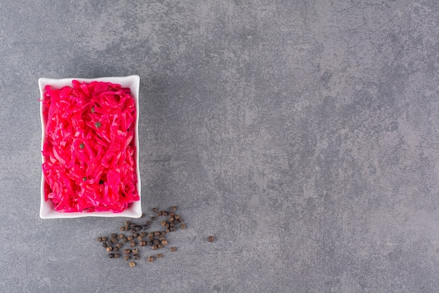 Fresh made portion of red coleslaw placed on stone table.