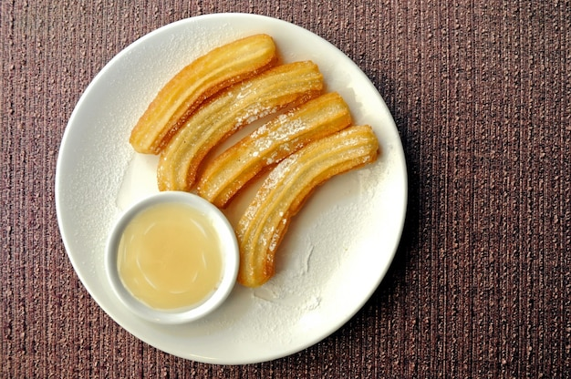 Fresh made spanish churros with white chocolate dipping suace