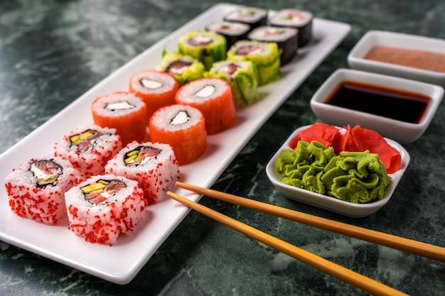 간장, 참깨 소스, 와사비, 절인 생강으로 만든 갓 만든 스시 롤 세트. 전통 일본 요리.