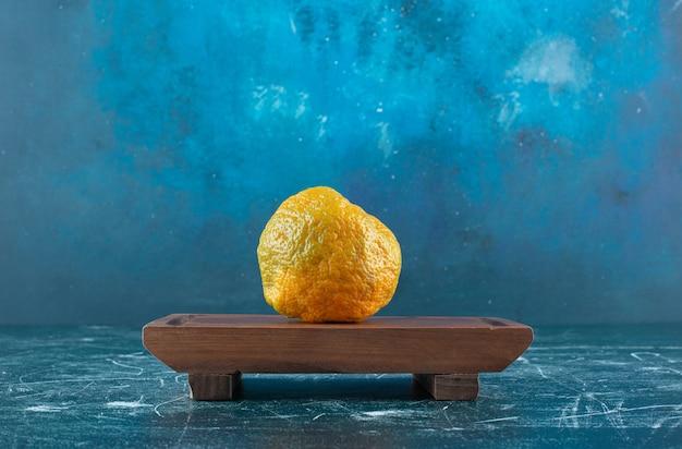 Fresh mandarin fruit on wooden board.