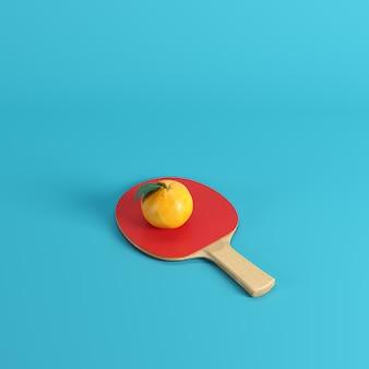 Fresh mandarin orange fruit or tangerine on ping pong paddle isolated on blue background
