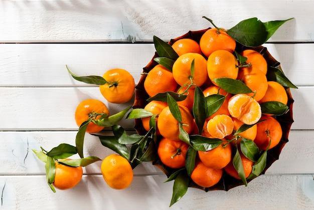 Свежие мандарины, апельсины или мандарины с листьями в деревянной коробке, вид сверху
