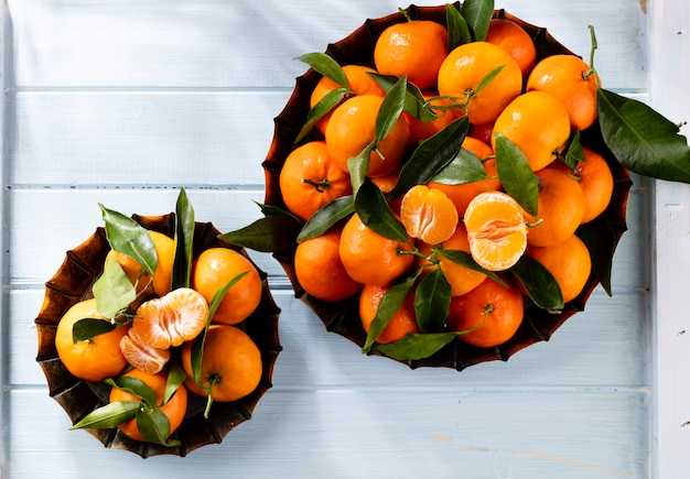 Fresh mandarin oranges fruit or tangerines with leaves in wooden box, top view