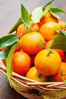 나무 테이블에 잎이 있는 신선한 만다린 오렌지 과일