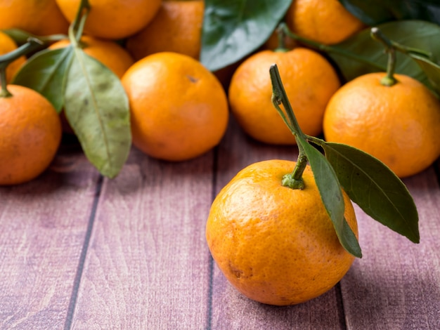 Fresh mandarin or tangerine with stems and leaves on a brown wooden surface copy space