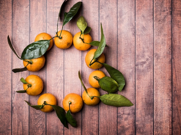 Fresh mandarin or tangerine with stems and leaves in the form of a circle on a brown wooden, copy space