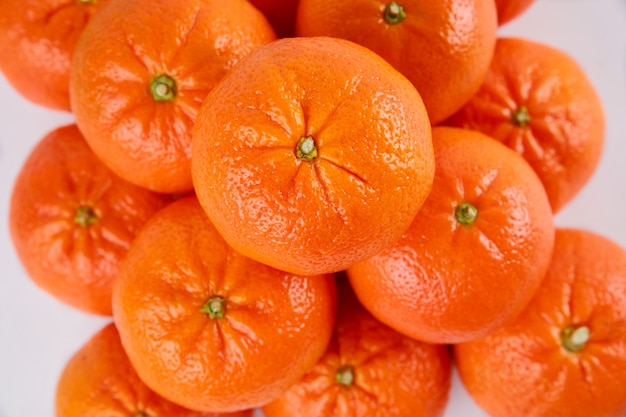 Fresh mandarin or tangerines on white background. top view, close up.