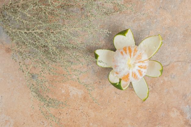 Mandarino fresco e pianta su sfondo marmo.