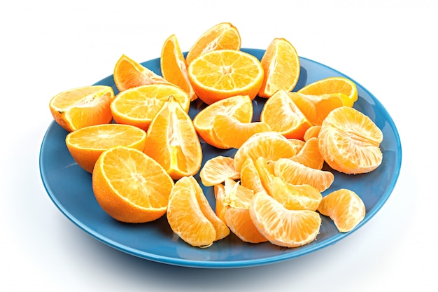 Fresh mandarins on a blue dish isolated on white