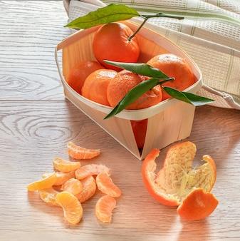 Свежие плоды мандаринов с листьями на деревянном столе