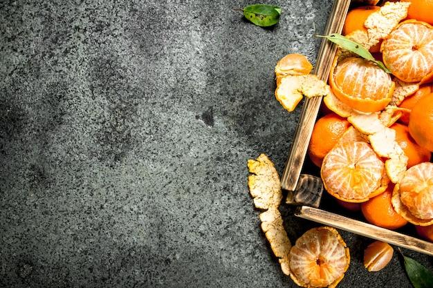 Свежие мандарины в старой коробке на деревенском столе.