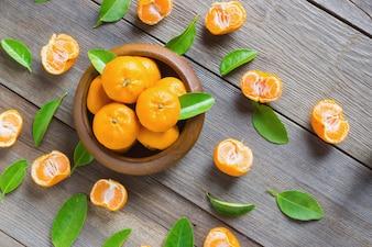 Fresh mandarins in wooden bowl