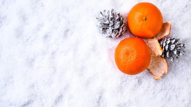 신선한 만다린, 오렌지, 포멜로, 금귤, 하얀 눈에 킨칸. 잘 익은 감귤류 배경. 새해와 크리스마스의 상징입니다. 복사 공간