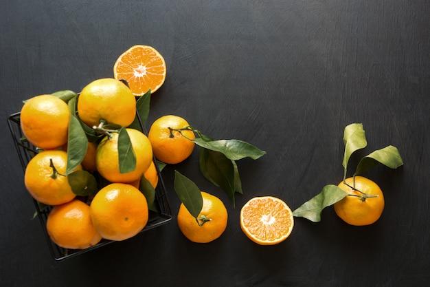 Fresh mandarins with leaves on black