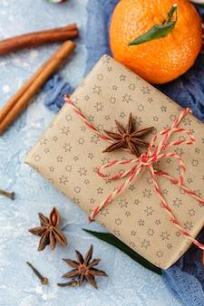 Свежие мандарины с листьями, леденцы, подарочные коробки в крафт-бумаге и специи - корица, анис и гвоздика